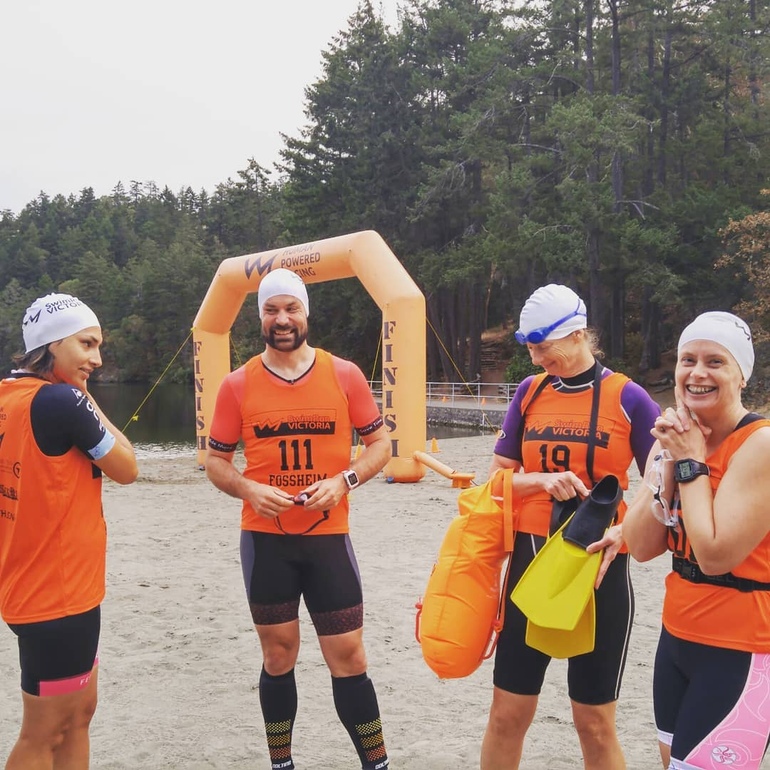 This is a photo of four people standing in a horseshoe shape beside thetis lake with an inflatable start and finish line in the background. They are all in swim caps and goggles.