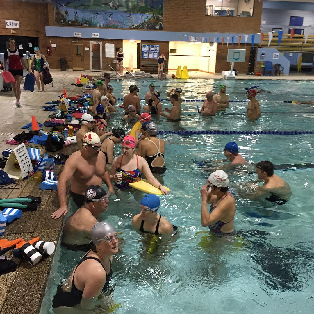 A large group of people in a swimming pool. Many are still standing in the water near the left deck getting ready. Most of them are also wearing swim caps and goggles.