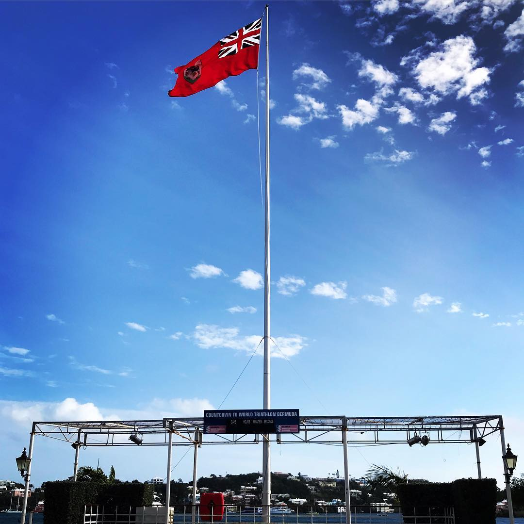 A tall flag pole with the red Bermuda flag at the top against a bright blue sky with some white clouds. Near the bottom a stage like structure is set up with metal poles and stage lights.