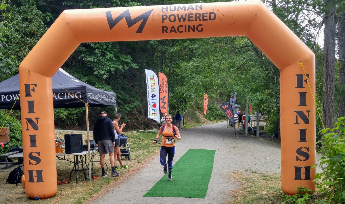 """Baylee wearing black tights and an orange top running through an orange inflatable finish line that reads """"Human Powered Racing"""" on the top. She is running on a gravel road with green trees behind her. She is smiling widely."""