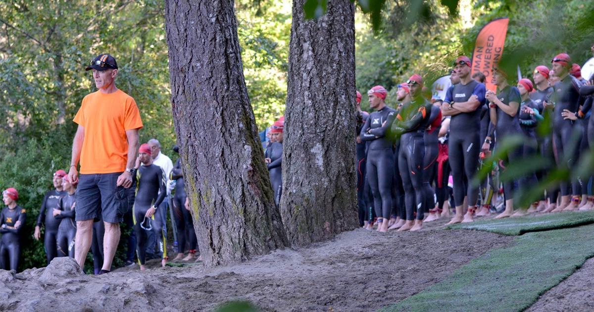 Rob is in the foreground to the left wearing shorts and an orange tshirt. Behind him is a forest and a crowd of triathletes in black wetsuits. The XTERRA and Human Powered Racing logos are on various athletes wetsuits and a flag in the distance.
