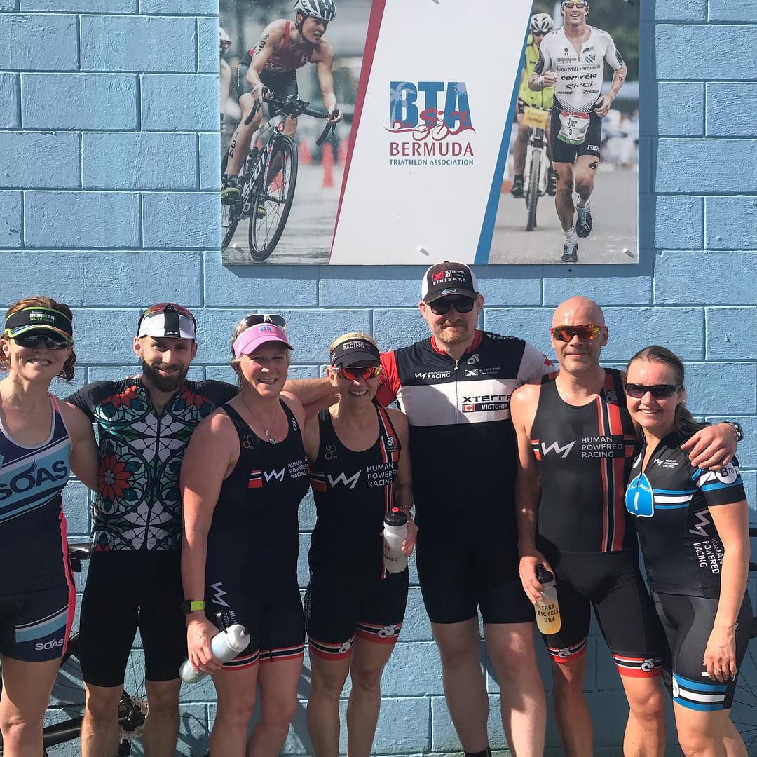 Group of people standing with their arms around each other against a blue brick wall. All are smiling and wearing black triathlon bodysuits.