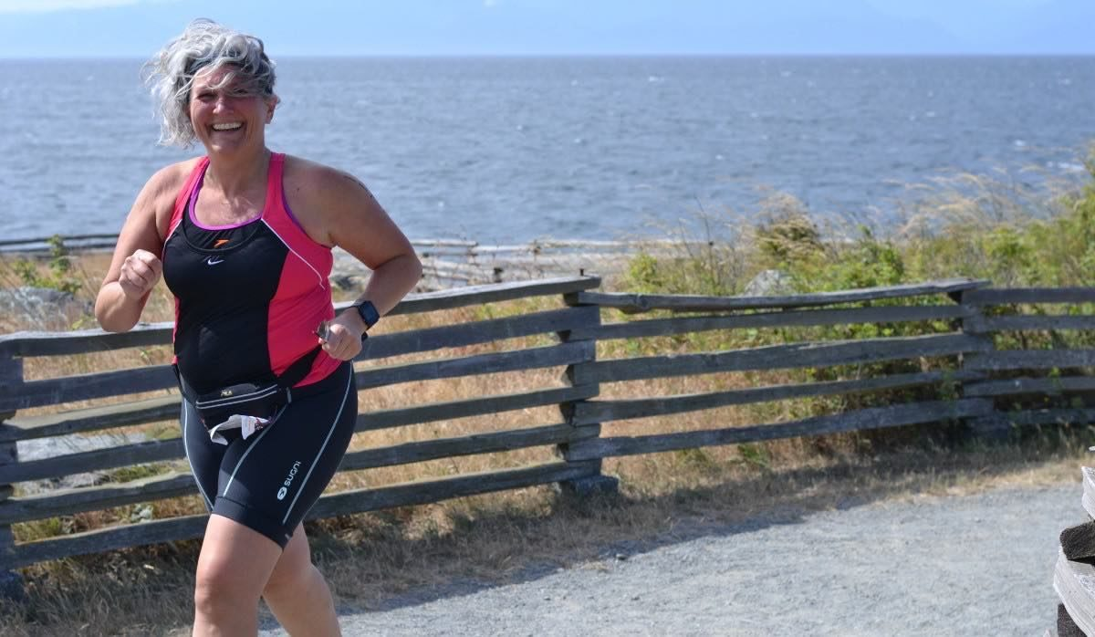 A woman in a black and pink triathlon body suit running and smiling at the camera. The ocean is behind her, and her hair is blowing in the wind.