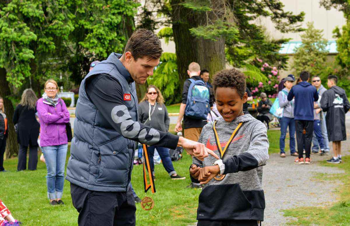Karsten Madsen talking to a young smiling athlete who is trying on his sports watch. There are people milling about and trees in the background.