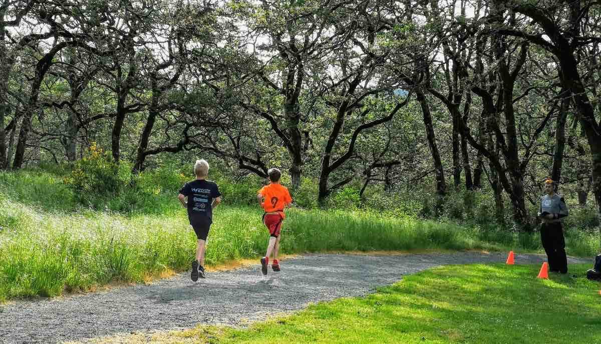 Two young people run away from the camera along a gravel trail with grass and trees on either side.