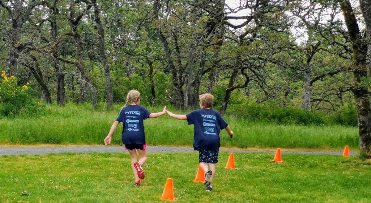 Two young people running away from the camera and high-fiving each other. They are in matching blue tshirts, and there are trees, grass, and orange pylons around them.