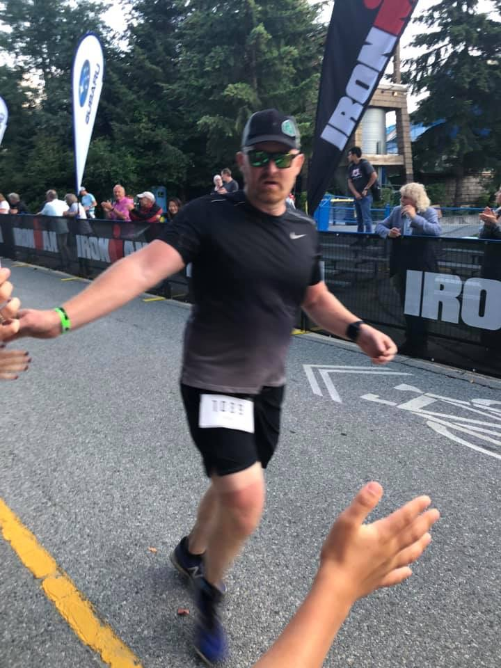 Mark Hopking running down finishing chute at Ironman Canada