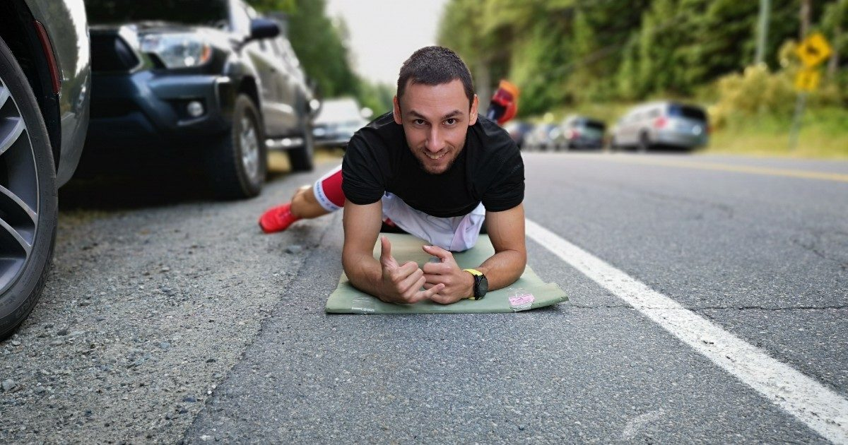 A man is in plank position on the ground facing the camera and smiling with his right leg out to the side.