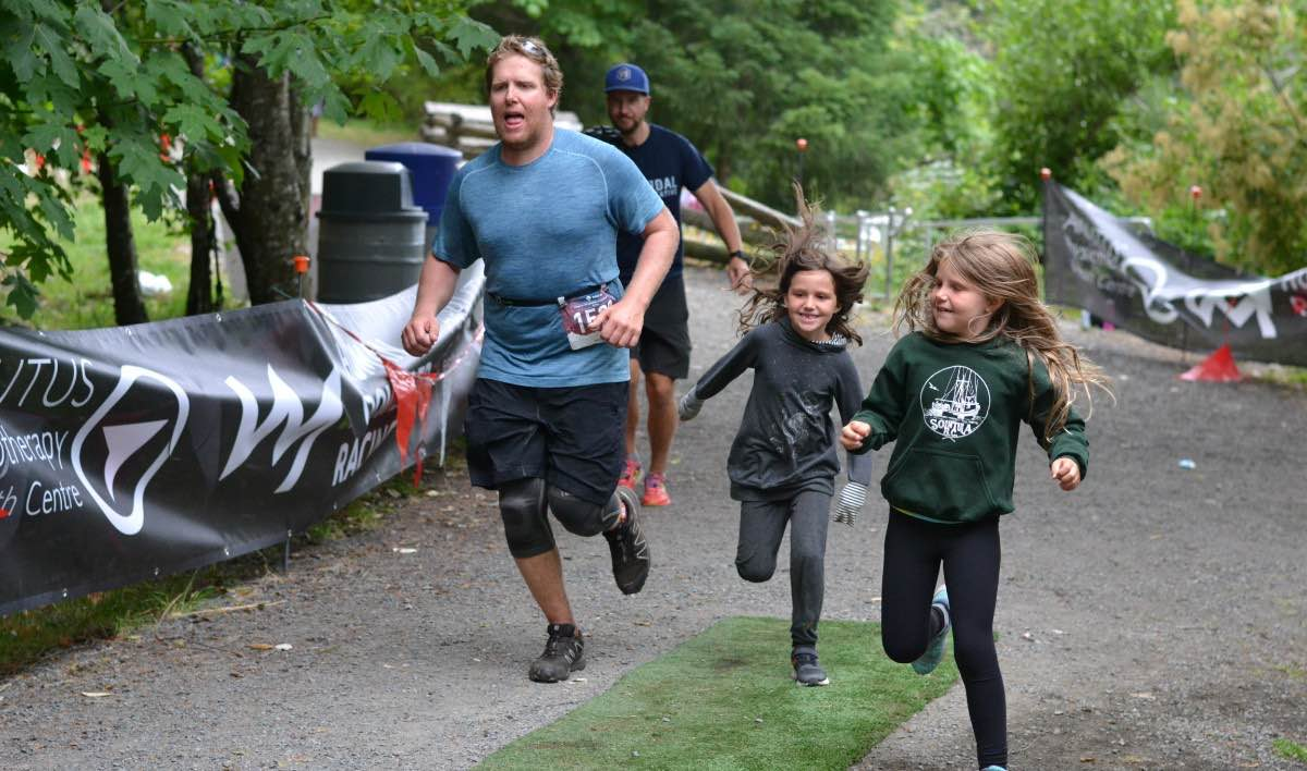 A man and two kids racing across the finish line smiling and looking tired.