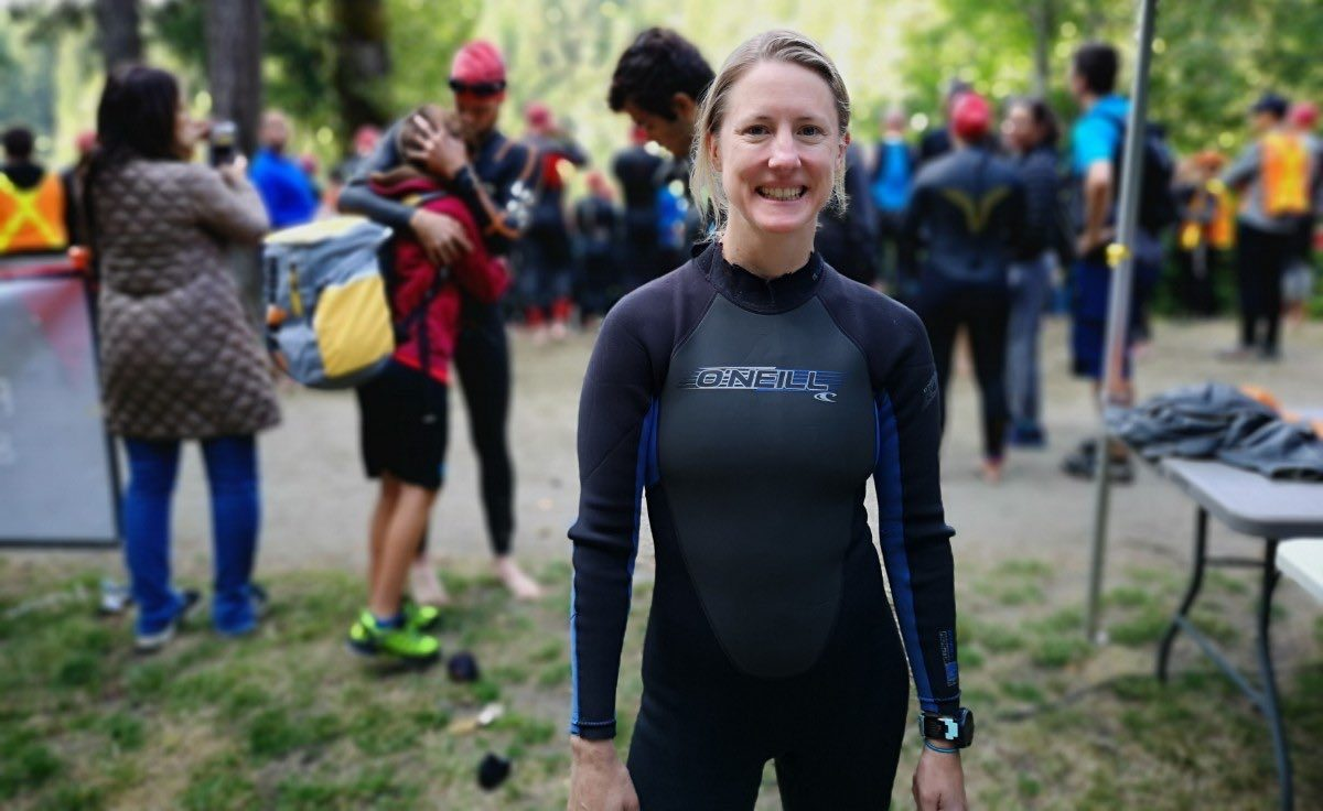 A woman in a wet suit with other athletes blurred out behind her smiling.