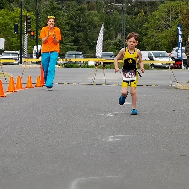 A young athlete runs towards the camera along a road marked with pylons.