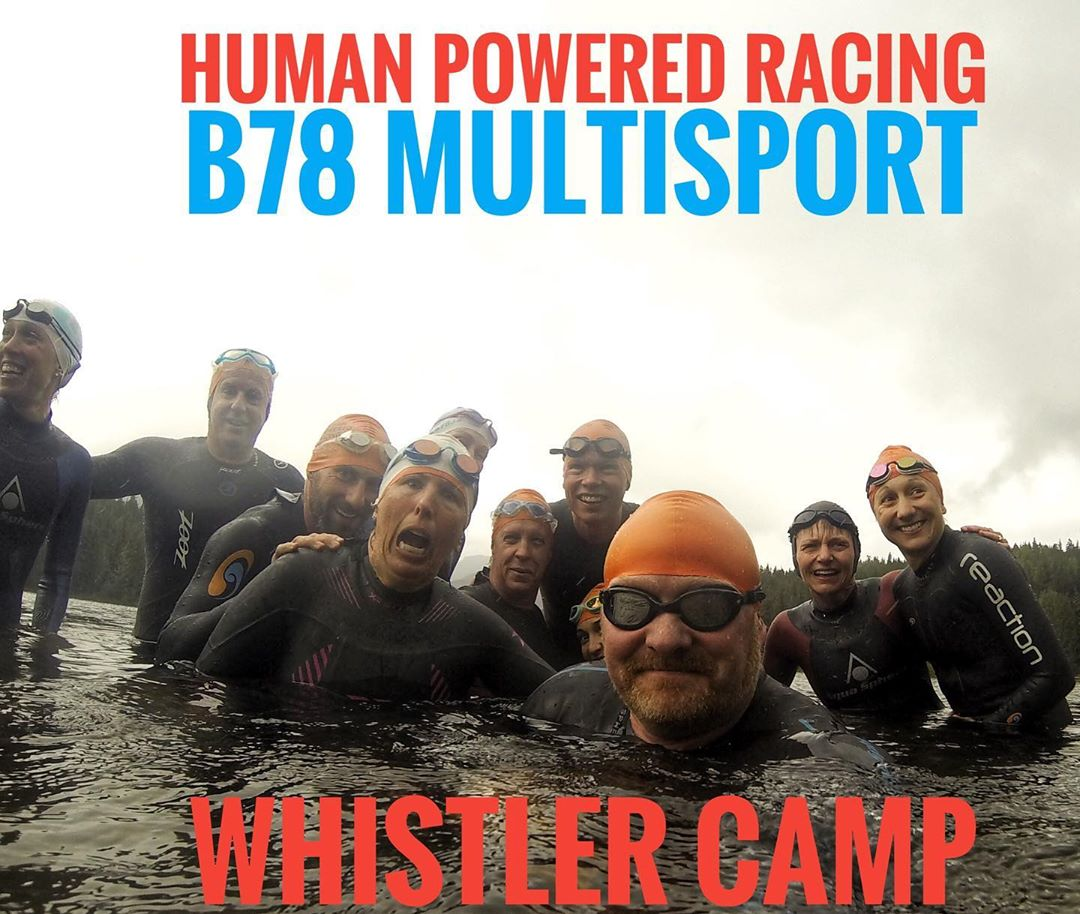 A group of athletes in wet suits and swim caps sticking their heads out of the water and smiling.