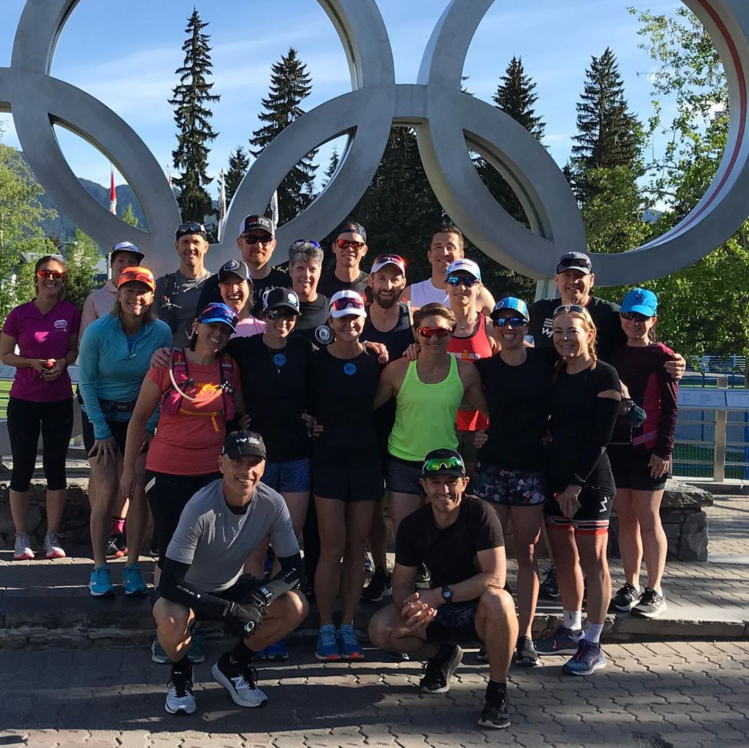 Group of people standing in front of olympic rings and smiling at the camera.