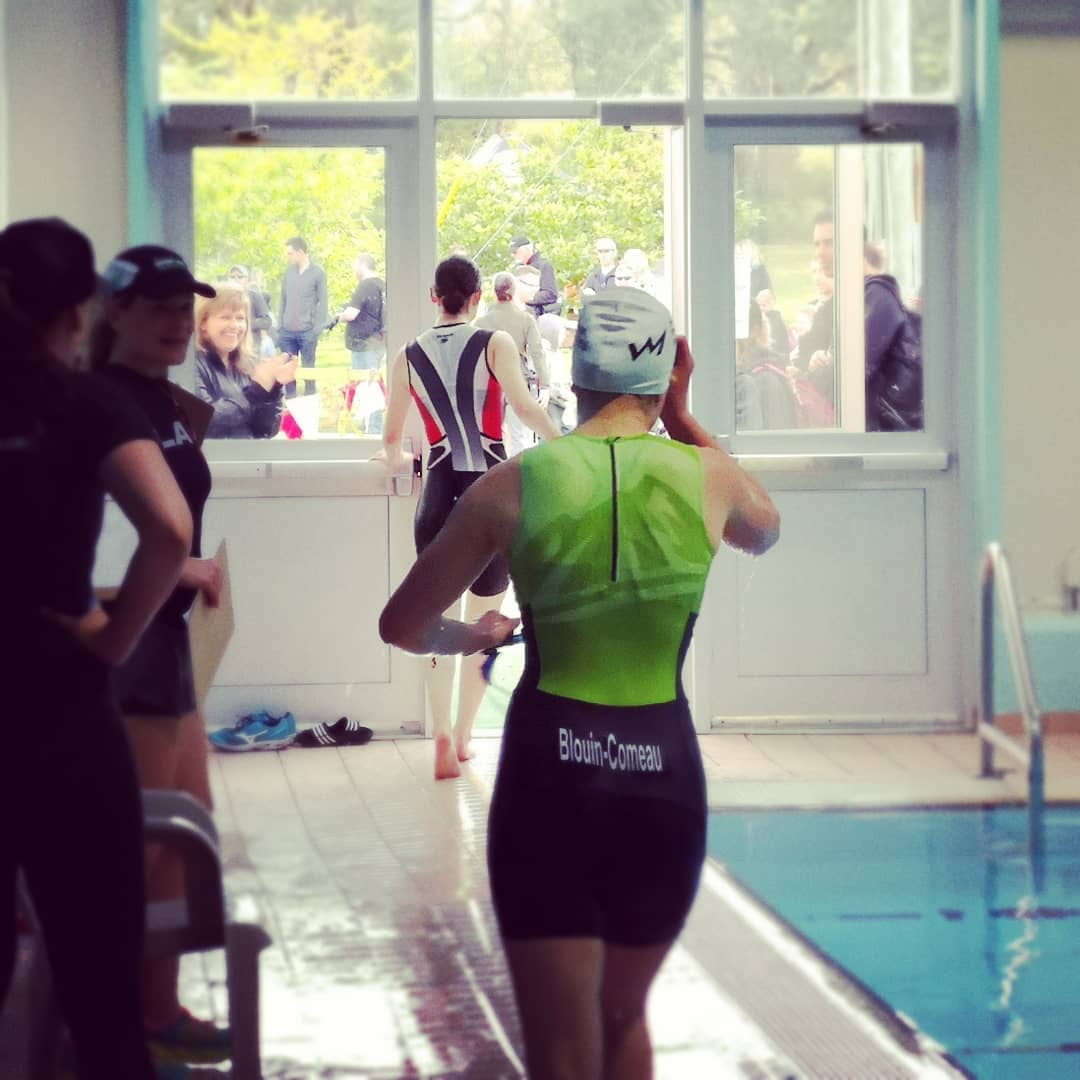 An athlete in a full body triathlon suit runs along a pool deck away from the camera.