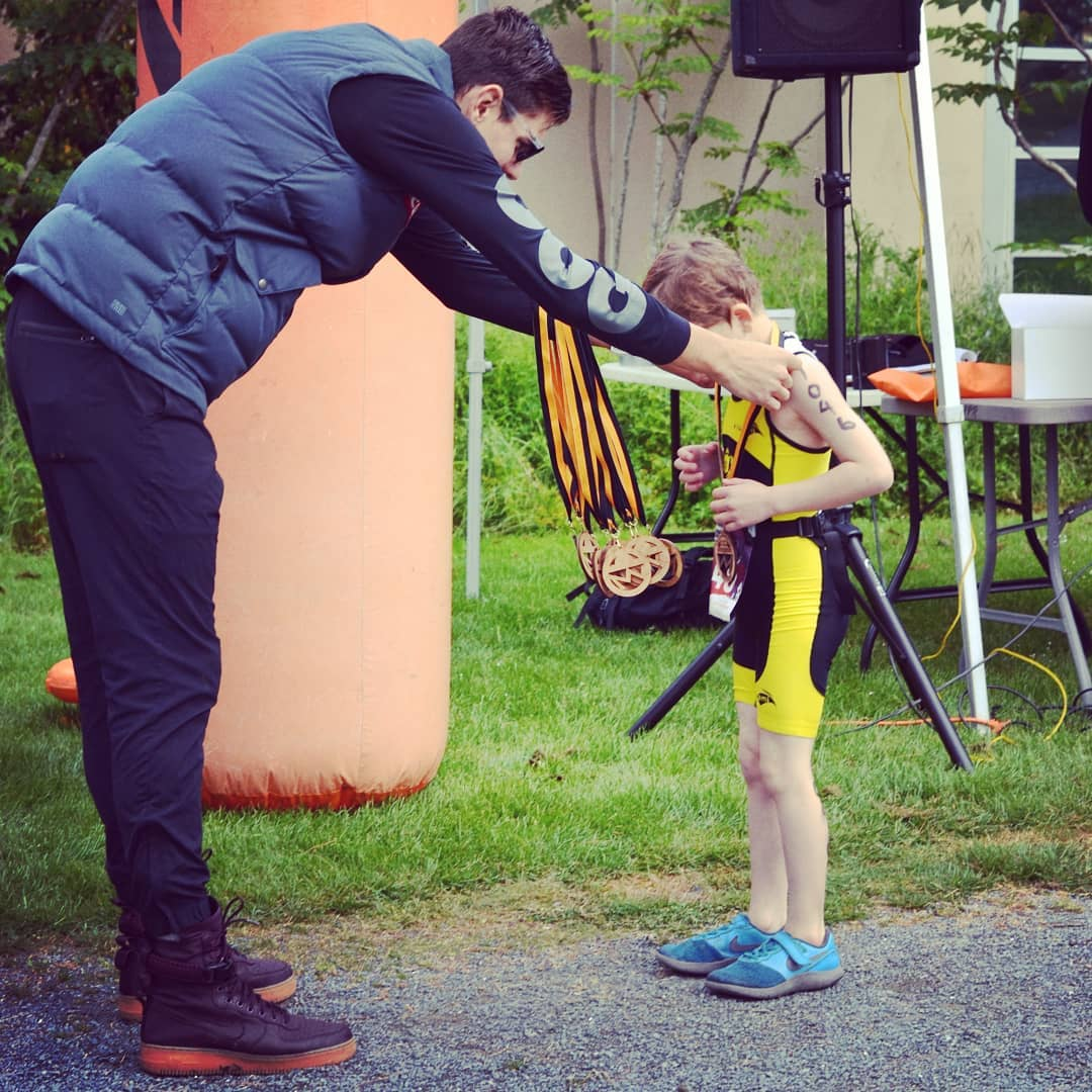 Karsten Madsen puts a metal on a young athlete at the finish line.