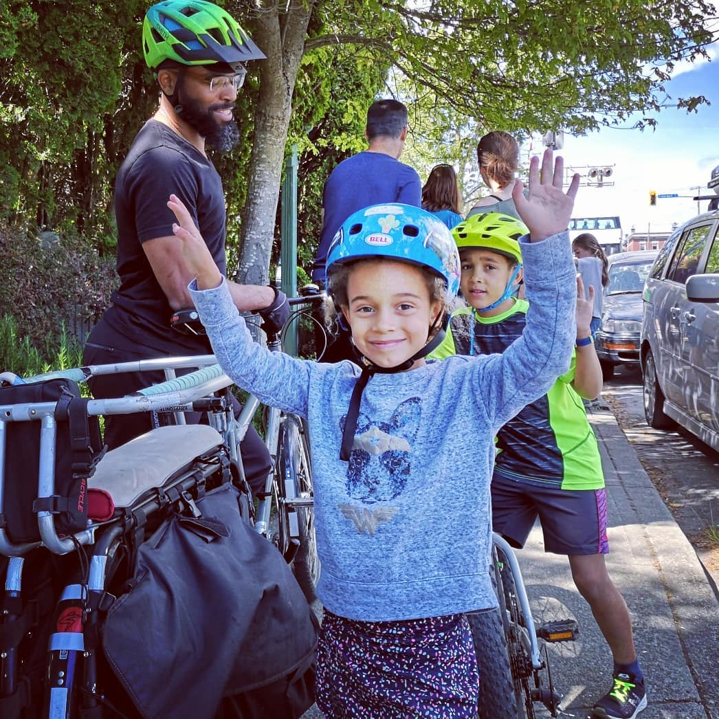 A young girl raises her arms above her head smiling with a helmet on and a bike beside her.