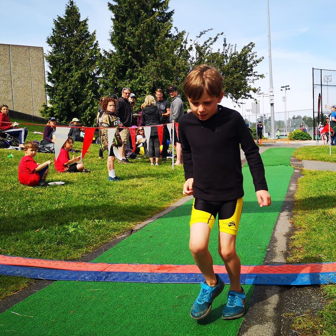 A young boy in yellow shorts hops over the finish line.