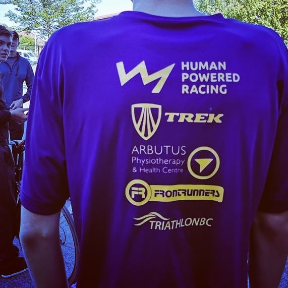 A purple tshirt with all the sponsor logos on the back being worn by a mannequin.