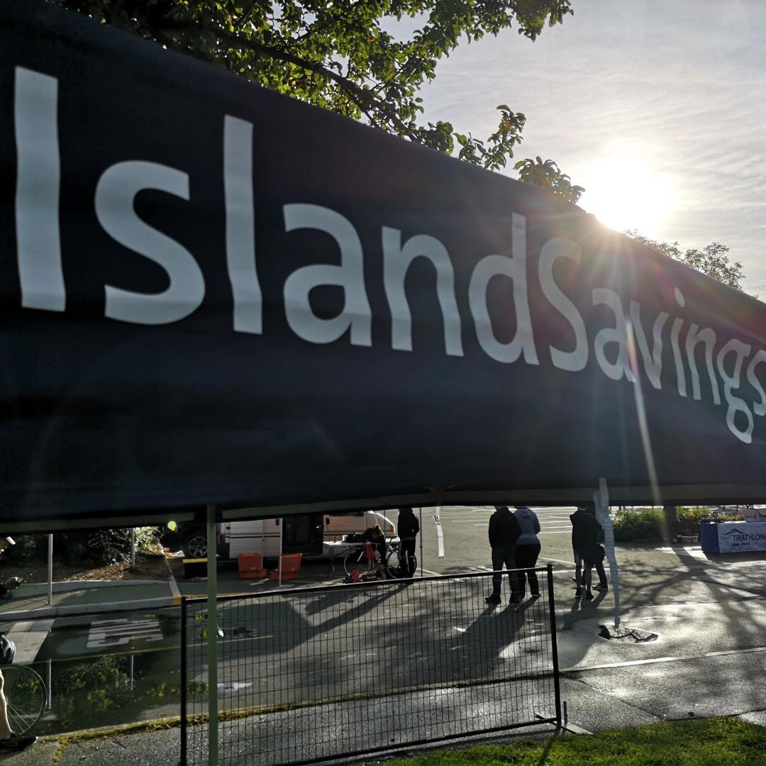 A black Island Savings Credit Union banner hung outdoors on a metal fence.