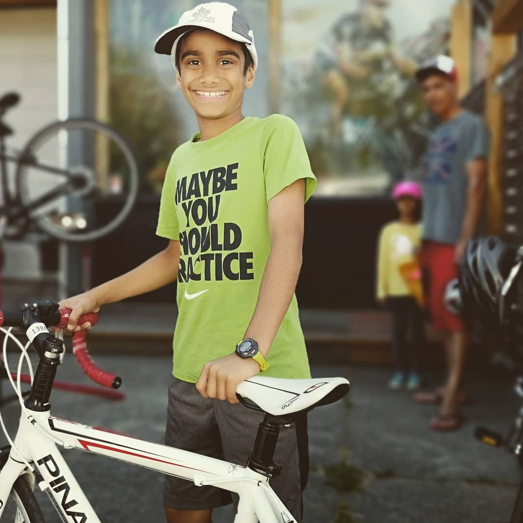 A young boy standing behind his bike and smiling out front of Trek cycles.