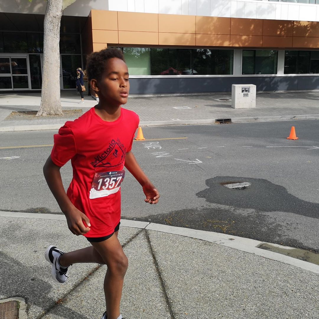 A young boy runs past the CARSA building on the UVic campus.