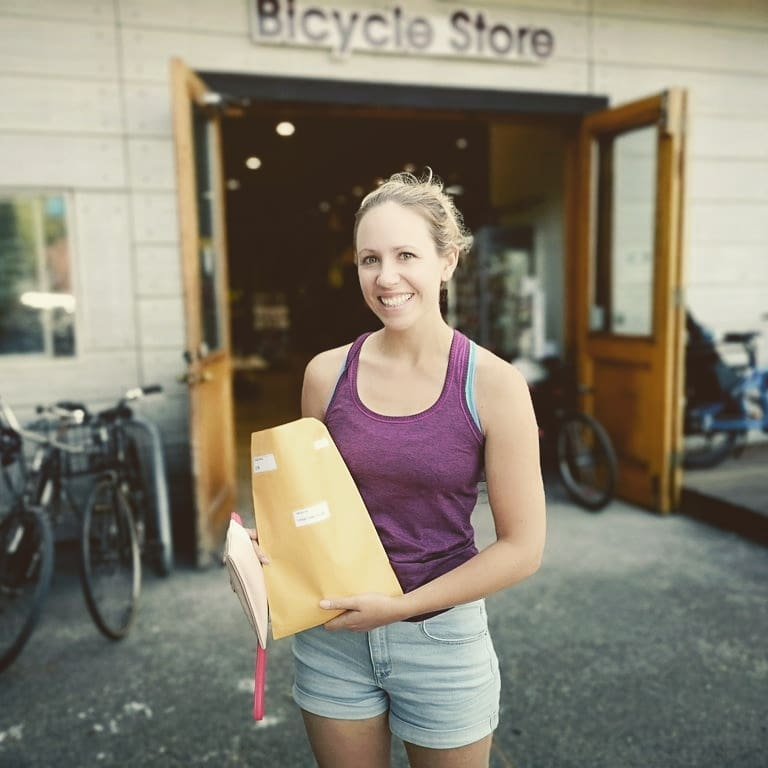 A woman smiling with her race package outside of Trek Cycles.