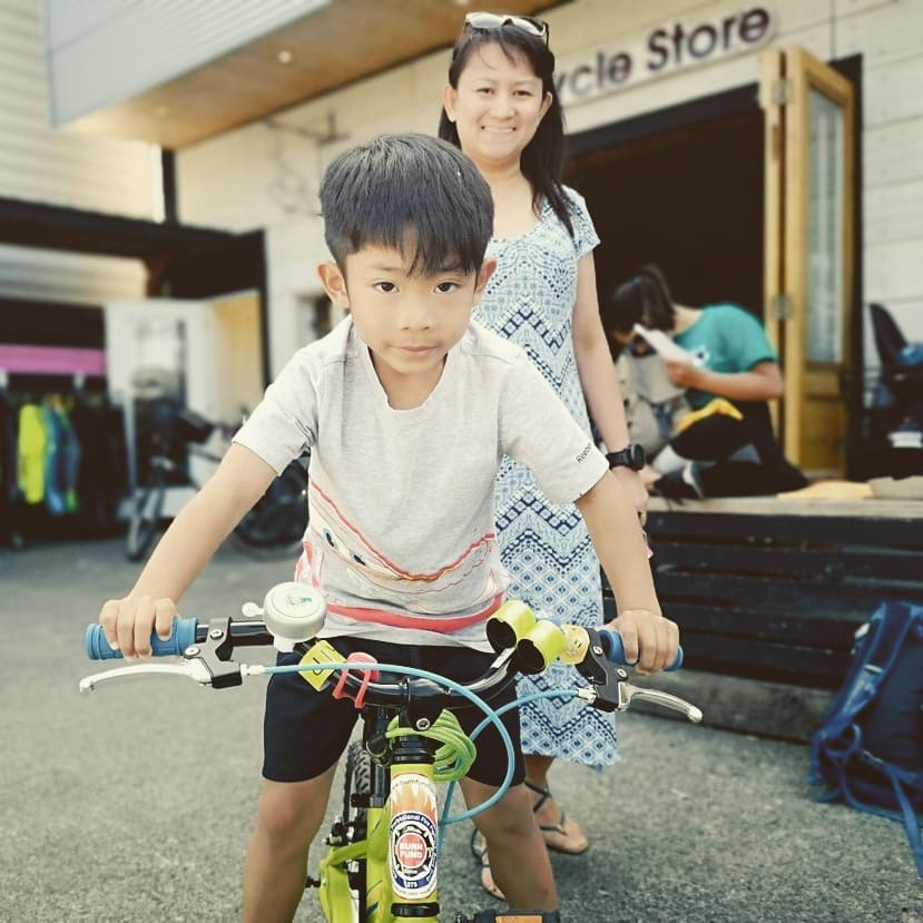A young boy smiling down at the camera from his bike out front of Trek Cycles with his mom smiling behind him.