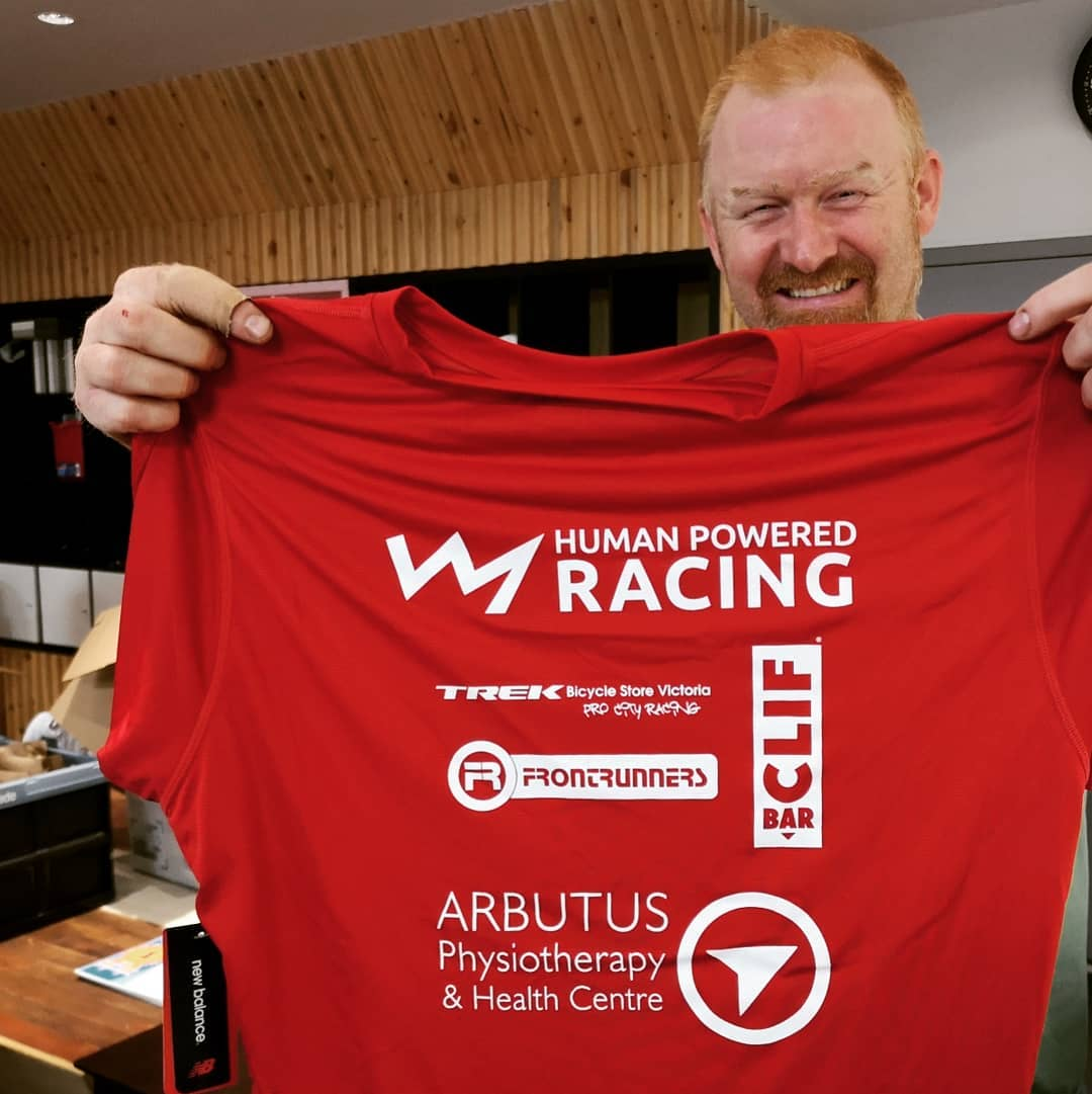 A man holding up a red XTERRA tshirt and smiling inside Trek cycles.