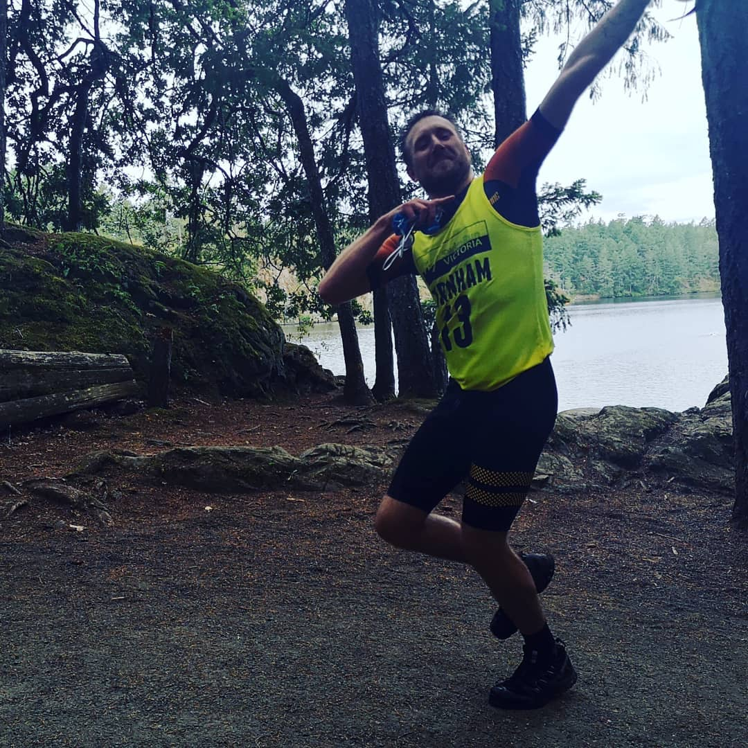 A man running on a forest trail raising his arms in celebratory salute for the camera.