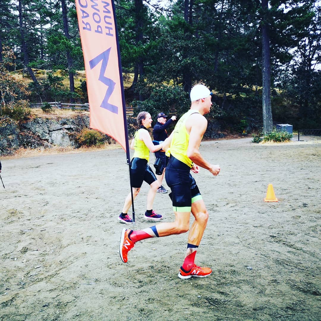 A man crossing a finish line on the beach at Thetis Lake.