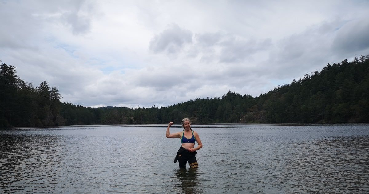 A woman stands smiling waist deep in a lake and flexing her right arm.