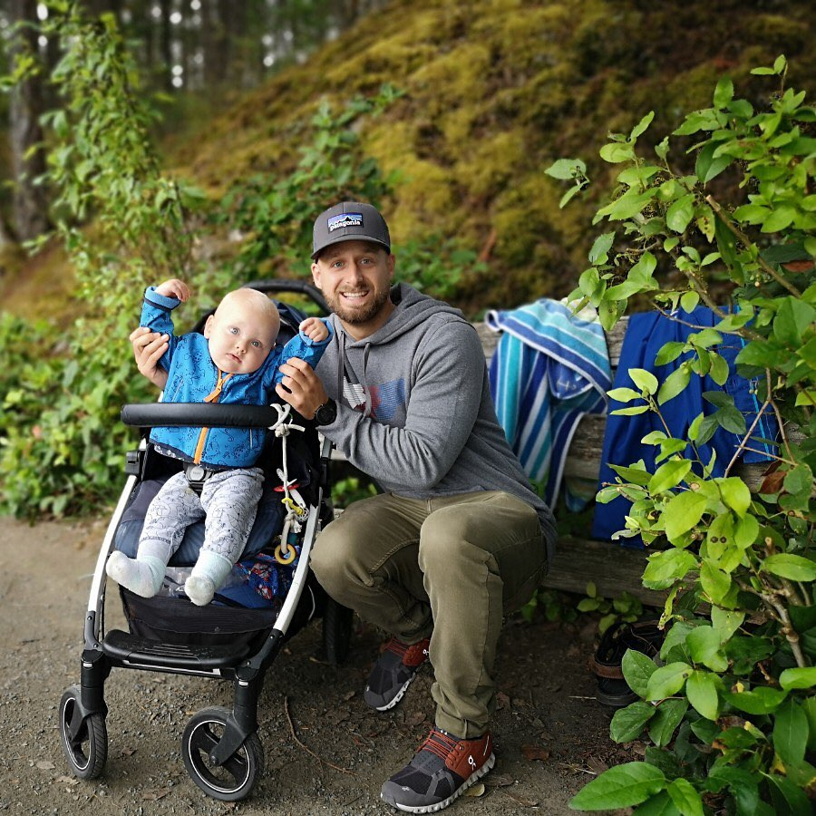 baby in a blue and grey outfit in a stroller and an adult, perhaps the father holds the baby's arms up to indicate cheering. Adult male is wearing a grey hat and grey sweatshirt with olive green pants. He is sitting on a bench with two blue towels hanging.