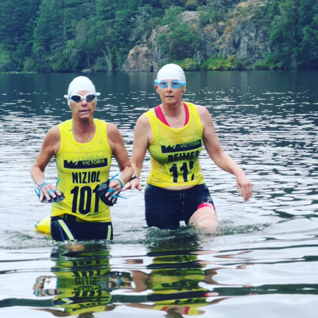 Two swimmers in yellow upper wear, black shorts, swim googles, white swim caps wade out of the water in the blue green lake, with the forest visible behind them on the far shore. They are thigh deep in the water and wear their race numbers in black on their clothes.