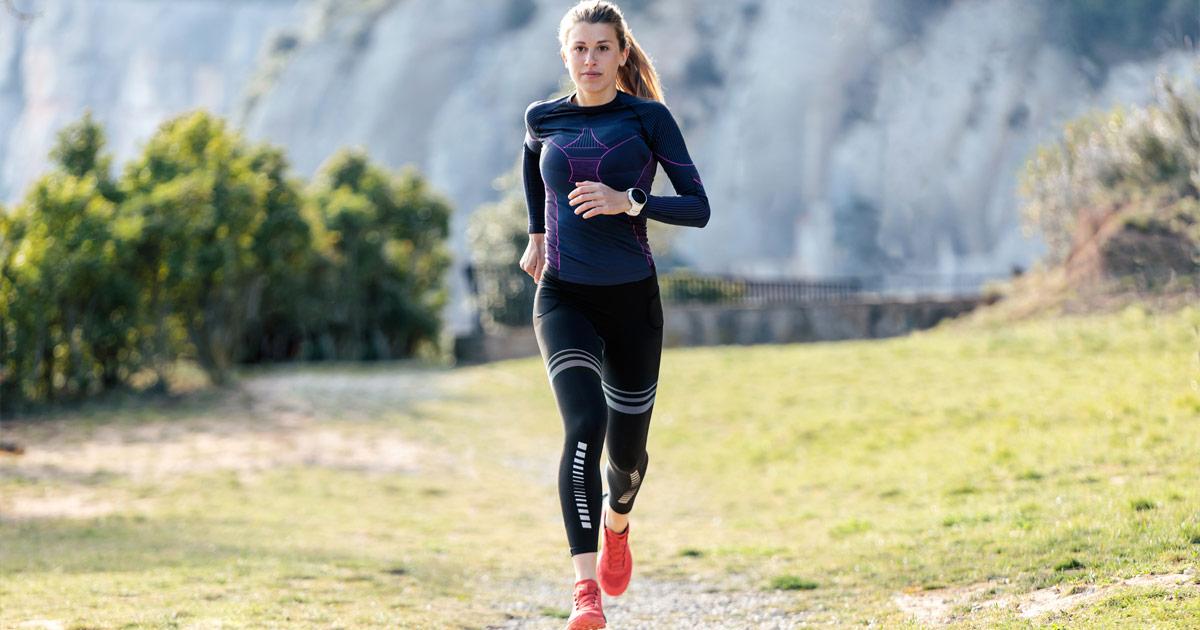A woman runs along a path in the mountains.