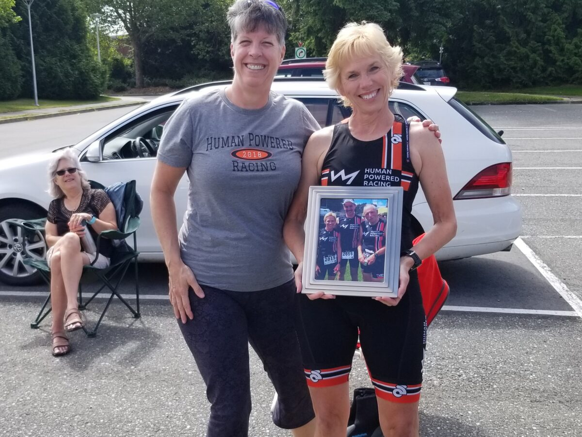 A group of three people with two in the front standing and one sitting behind in a camping chair to the left. The two standing smile holding a picture frame wearing triathlon gear. These people are: Nancy Carleton (left standing), Carol Richer (right standing), Marsha Petty-Johnson (back seated). The picture they are holding is of Carol Richer and Justin Martin at the 2014 Tri of Compassion standing with one other racer. They are both photos taken outside.