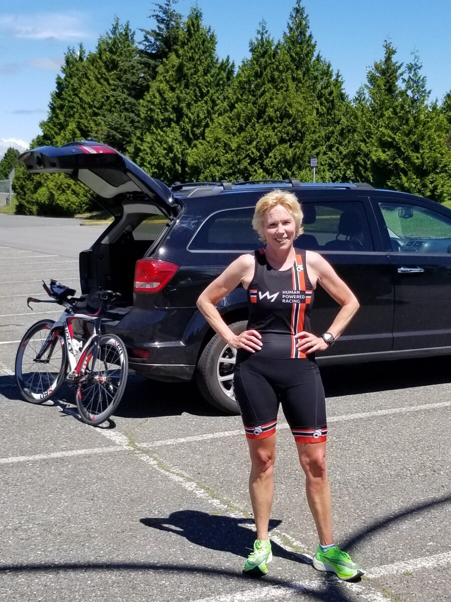 Nancy Carleton stands outside with her bike propped up on the back of a black car behind her. Another race done!