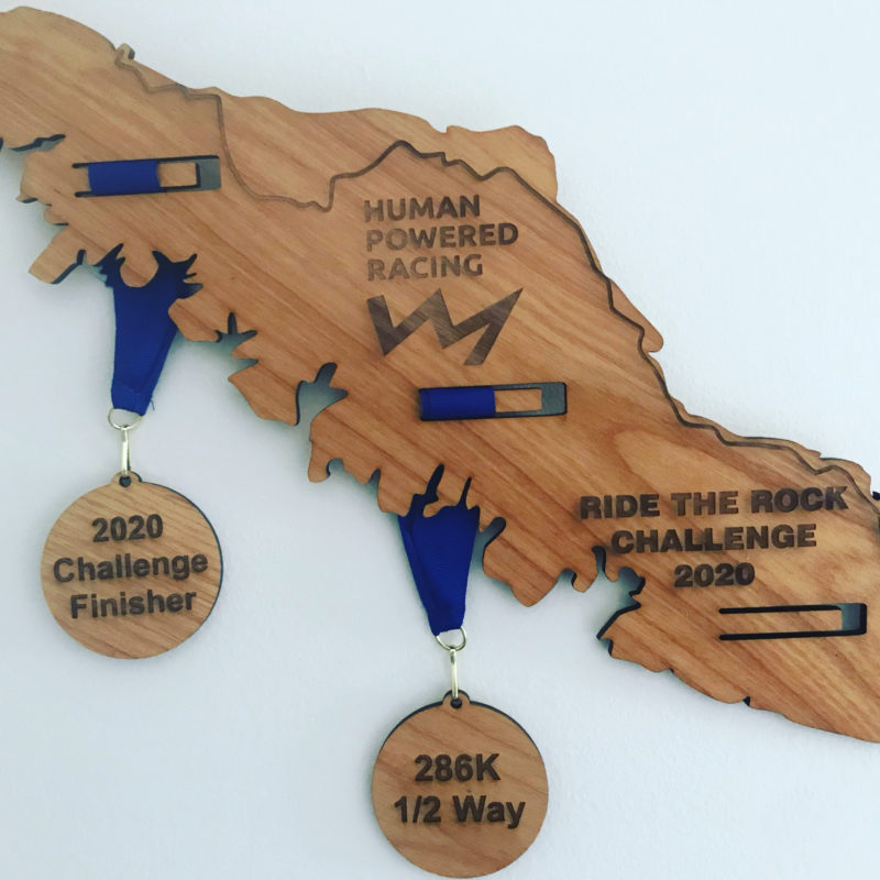An image of the Ride the Rock plaque with the 1/2 way and finisher medals attached.