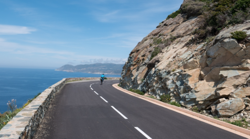 A cyclist riding a coast road on Corsica