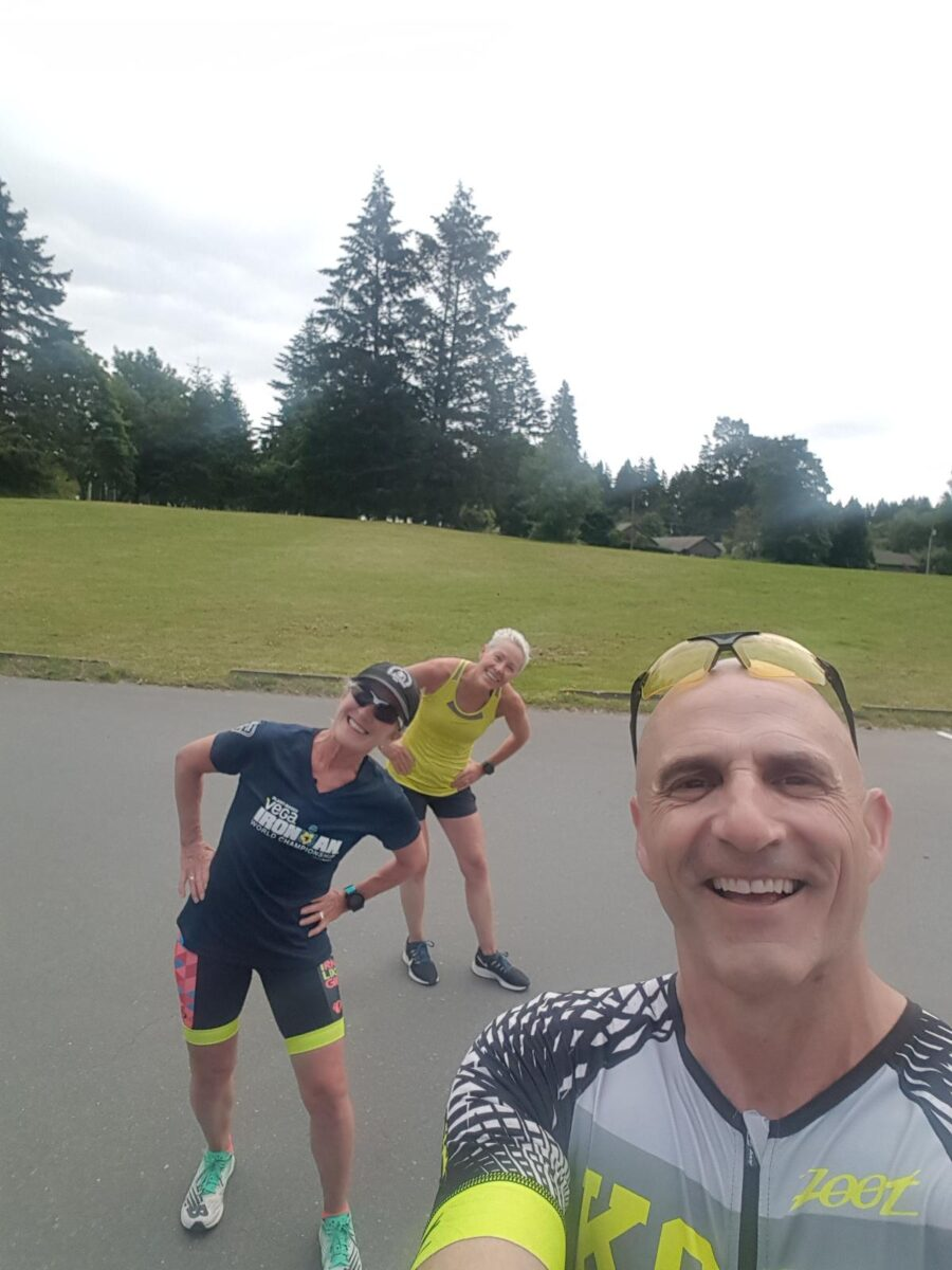 Michael Campbell, Jennifer Campbell and Donna Morrissey (listed from front to back) stand outside on pavement with grass and forest behind at Elk Lake. They are smiling in their triathlon gear and spread out (approx. 2 meters apart).