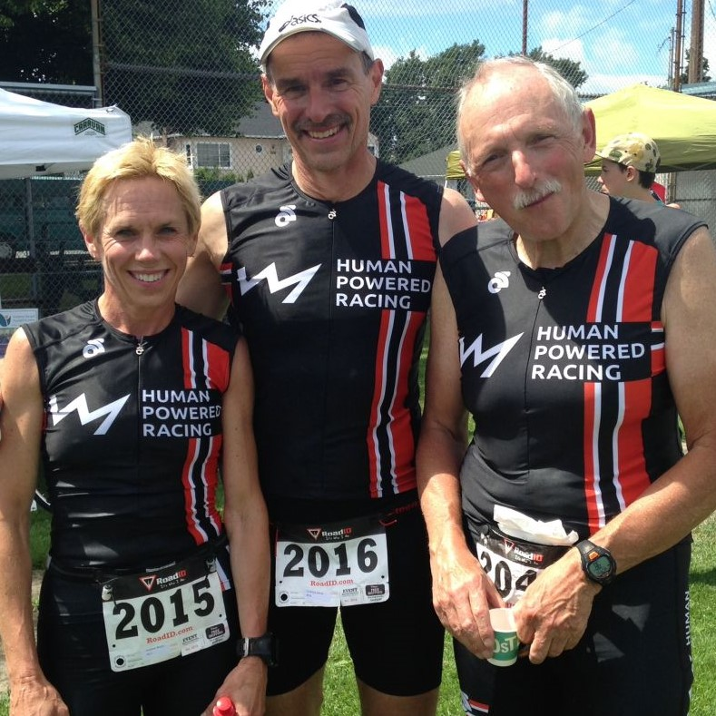 Nancy Carleton and Justin Martin at the 2014 Tri of Compassion standing with one other racer. All wear Human Powered Racing Red, Black, and White gear. They are outside in a field.