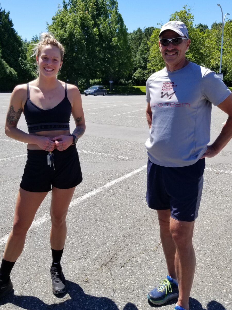 Gillian Carleton stands in a parking lot in black athletic clothes next to David Carleton wearing a grey tshirt and black shorts.