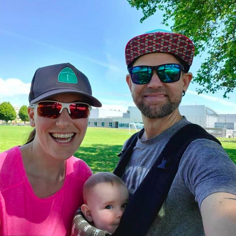 Barbara Rober stands smiling to the left in pink shirt and a cap next to her partner wearing sunglasses, a cap, and a tshirt. Between them in a carrier on her partner's chest is a small baby looking at the camera. They are in a field with a grey-blue building and blue skies behind them.