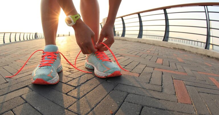 Runner laces up her shoes by the water.
