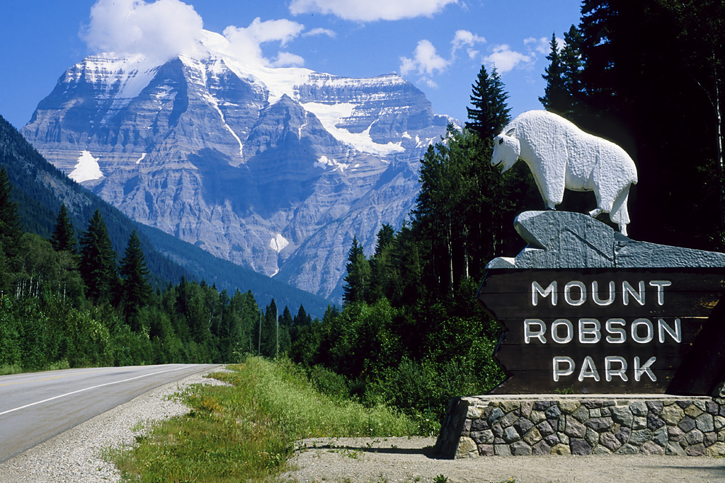 Image of the park sign at the entrance to Mt Robson park with the mountain in the background.